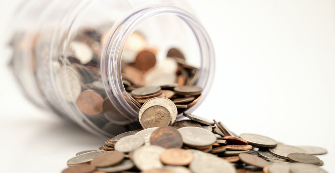 Coins and a fallen jar illustrate how you can make an extra income