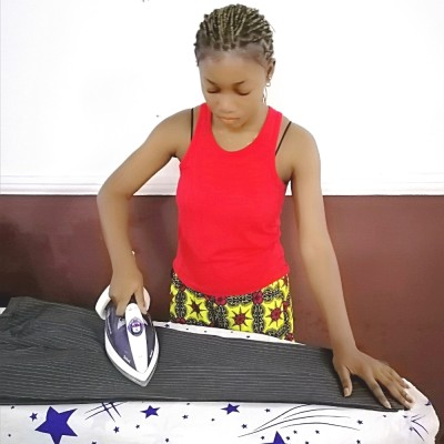 A photo of a lady ironing a pair of pants or trousers on a ironing board